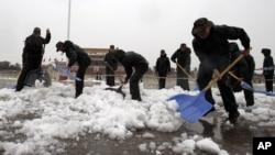 Cảnh sát bán quân sự Trung Quốc xúc tuyết tại Quảng trường Thiên An Môn ở Bắc Kinh, ngày 4/11/2012.