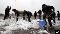 Petugas dari kepolisisan Tiongkok membersihkan salju yang menyelimuti lapangan Tiananmen di Beijing (4/11).