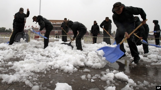 Chinese paramilitary police shovel snow accumulated on Tiananmen Square in Beijing, November 4, 2012.