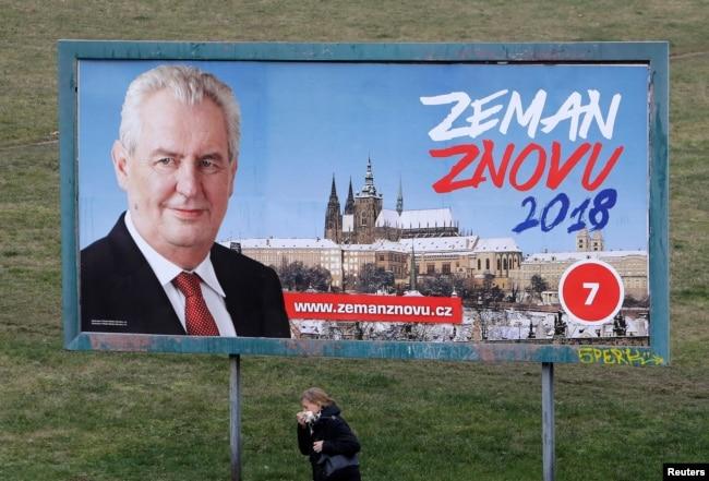 "A woman walks past a presidential election campaign poster of incumbent Milos Zeman in Prague, Czech Republic, Jan. 11, 2018. The poster reads: ""Zeman again 2018""."