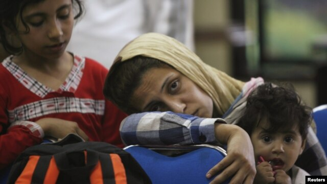 Asylum seekers wait in a police station in Surabaya , East Java province, July 29, 2012.