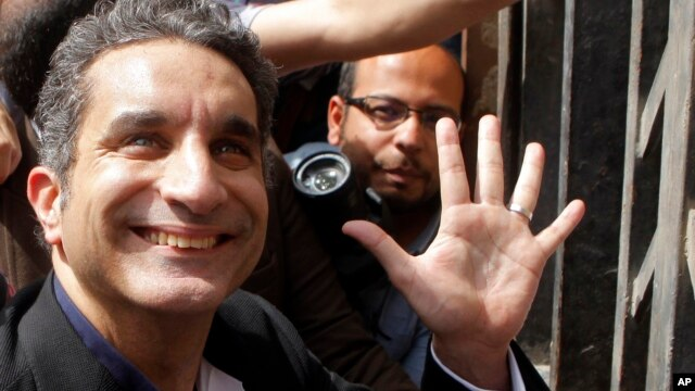 Bassem Youssef waves to his supporters as he enters Egypt's state prosecutors office in Cairo, Mar. 31, 2013.