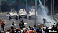 "Opposition demonstrators face military vehicles near the Generalisimo Francisco de Miranda Airbase ""La Carlota"" in Caracas, Venezuela, April 30, 2019."