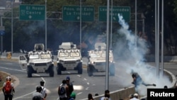 委内瑞拉反对派示威者在加拉加斯一处空军基地外与军车对峙。(2019年4月30日)