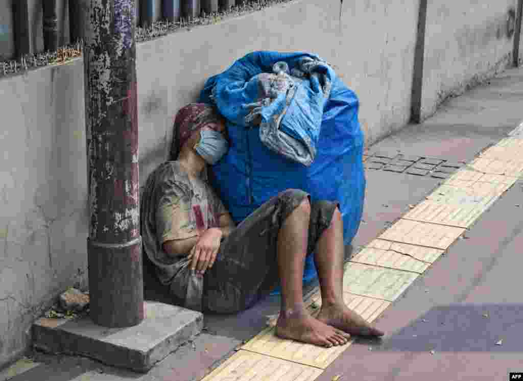 A man takes a nap on the pavement in downtown Jakarta.