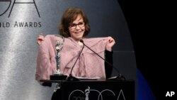 """Sally Field holds up a sweater worn by her character in """"Forrest Gump"""" as she presents the career achievement award at the 20th annual Costume Designers Guild Awards at The Beverly Hilton hotel on Tuesday, Feb. 20, 2018, in Beverly Hills, California."""