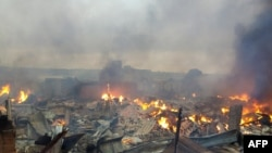 Les ruines en feu du marché de Bouaké le 27 août 2019 suite à un incendie dans la nuit (Photo par - / AFP)