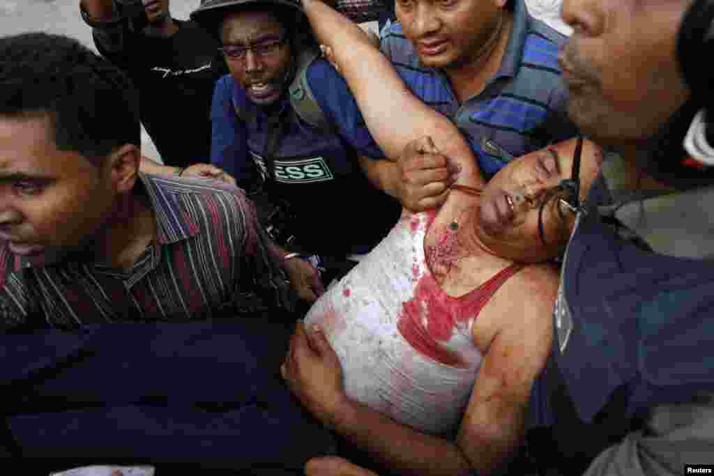 Members of the media assist an injured police officer during a clash with activists of Hifazat-e-Islam in front of the national mosque in Dhaka, May 5, 2013.