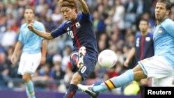 El japonés Keigo Higashi (10) lanza un disparon que el español Alvaro Dominguez intenta bloquear. Japón dio la sorpresa al derrotar a la favorita España, 1-0.