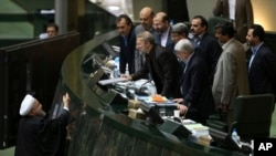 FILE - Iranian President Hassan Rouhani, left, presents a draft of the country's new budget and sixth development plan to the parliament speaker in an open session of parliament, in Tehran, Iran, Jan. 17, 2016.