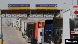 FILE - Trucks wait in a long queue for border customs control to cross into the U.S. at the Otay border crossing in Tijuana, Mexico, Feb. 2, 2017.
