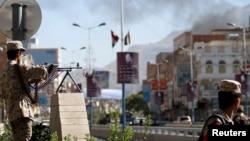 Seorang tentara mengarahkan senapan mesinnya ke jalan yang menuju Kementerian Pertahanan di menyusul serangan di Sana'a (5/12).