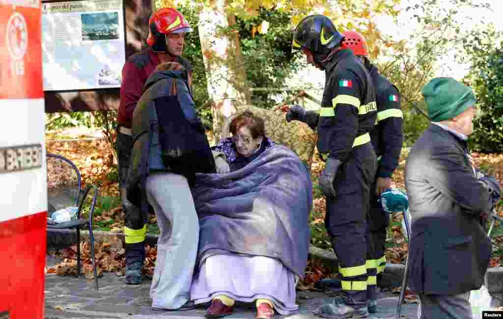 Petugas pemadam kebakaran mengevakuasi seorang perempuan menyusul gempa di Norcia, Italia (30/10). (Reuters/Remo Casilli)
