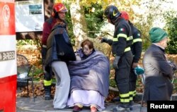 Firefighters take care of a woman following an earthquake in Norcia, Italy, Oct. 30, 2016.