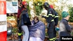 이탈리아 소방관들이 30일 지진이 발생한 중부 지역에서 피해자들을 돌보고 있다.