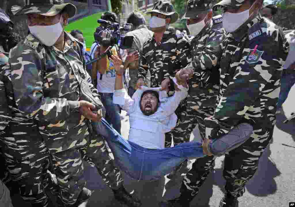 Pripadnici paravojnih snaga privode aktivistu u Nju Delhiju, koji protestuje zbog ubistva četvoro poljoprivrednikau državi Utar Pradeš, koje je pregazilo vozilo čiji je vlasnikministar unutrašnjih poslova Indije (Foto: AP/Manish Swarup)