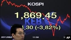 一名首尔的银行外汇交易员8月8日在韩国股市电子看版前走过
