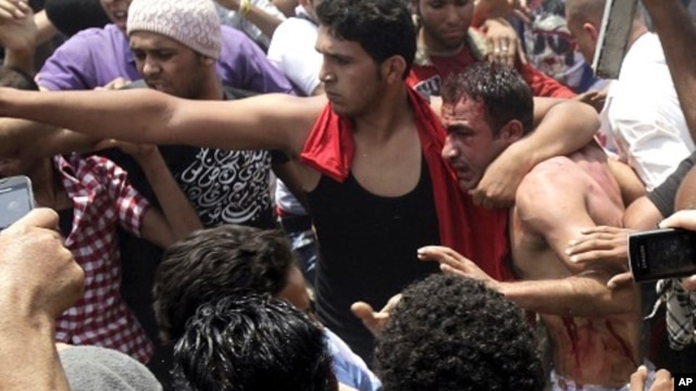 """A protester protects a detained """"thug"""" from other protesters who want to beat him during clashes between Islamist protesters and armed """"thugs"""" in Cairo May 2, 2012."""