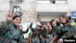 Kurdish female fighters of the Women's Protection Unit gesture in the Sheikh Maksoud neighborhood of Aleppo, Syria, Feb. 7, 2018.