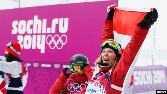 Winner Canada's Dara Howell (R) celebrates with the Canadian flag as compatriot and third-placed Kim Lamarre looks on after the women's freestyle skiing slopestyle finals at the 2014 Sochi Winter Olympic Games in Rosa Khutor, Feb. 11, 2014.