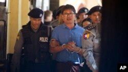 Reuters journalist Wa Lone is escorted by police as he leaves court outside Yangon, Myanmar, Jan. 10, 2018.