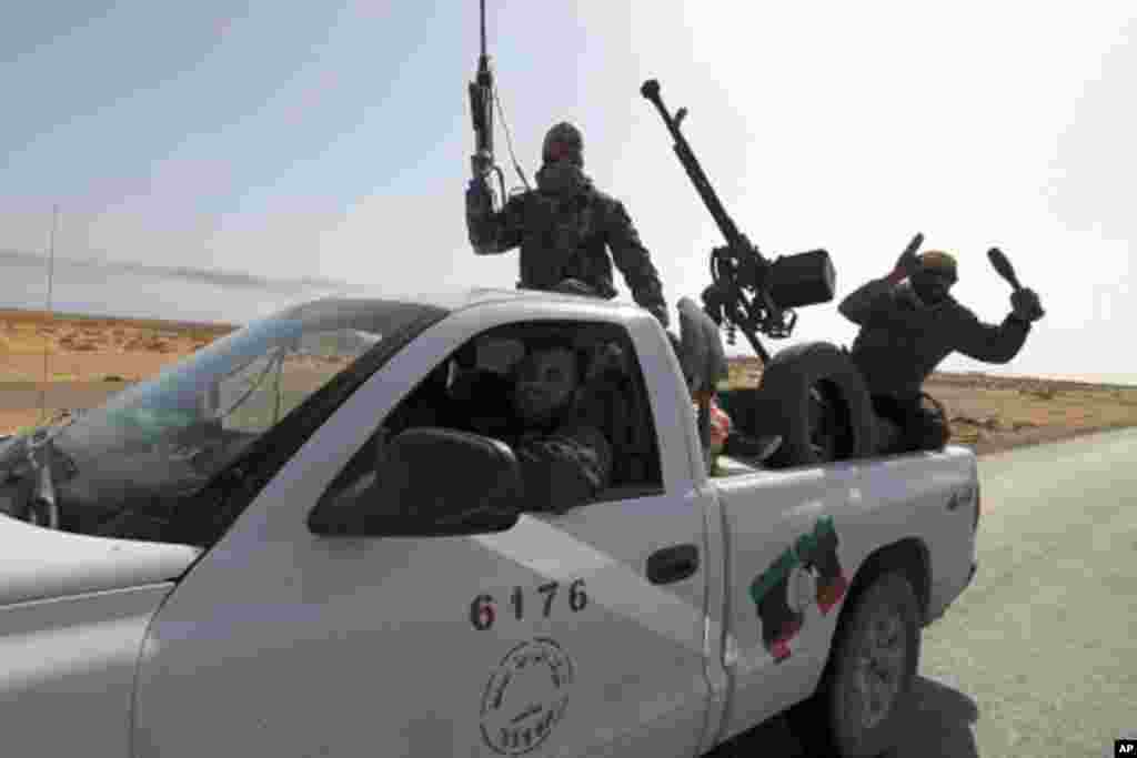 Rebels travel in a convoy on their way to Sirte city near Bin Jawad, March 28, 2011