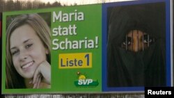A poster of the Swiss People's Party (SVP) campaign for stringent immigration laws is placed beside a road in the town of Bremgarten, south of Zurich, Switzerland. The poster reads: 'Maria not Sharia !'. (file photo)
