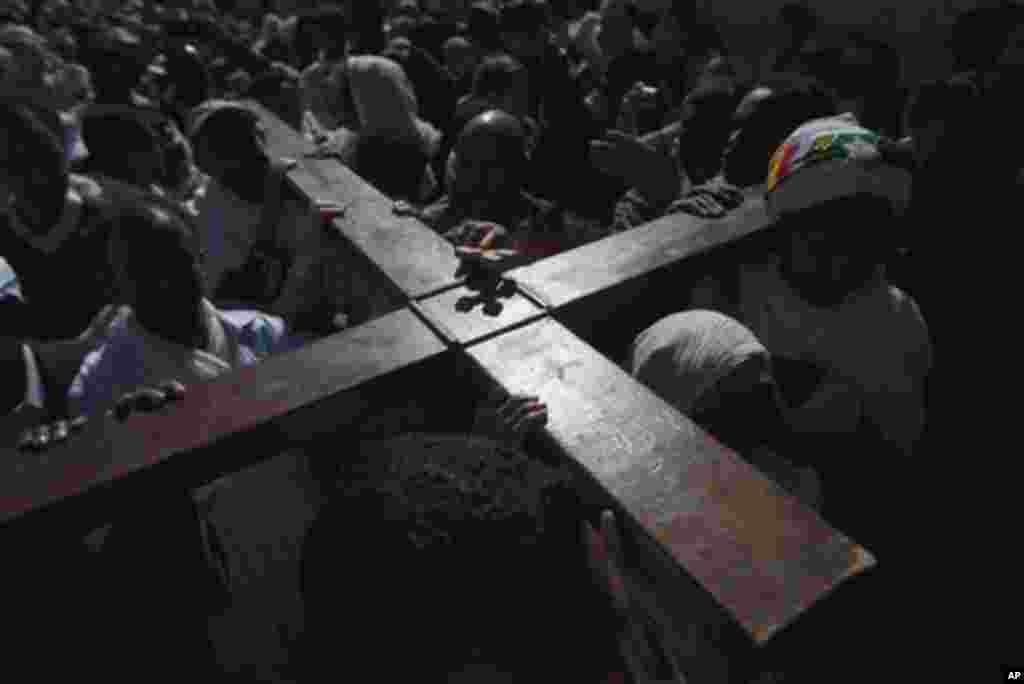 Ethiopian Orthodox Christian worshippers carry a cross during Good Friday processions towards the Church of the Holy Sepulchre, traditionally believed to be the burial site of Jesus Christ, in Jerusalem's Old City, Friday, April 13, 2012. (AP Photo/Sebast