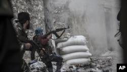 2012年10月24日﹐在阿勒頗市一處戰場﹐一名敘利亞反政府武裝人員在對方火力襲擊下急忙退入掩體後。