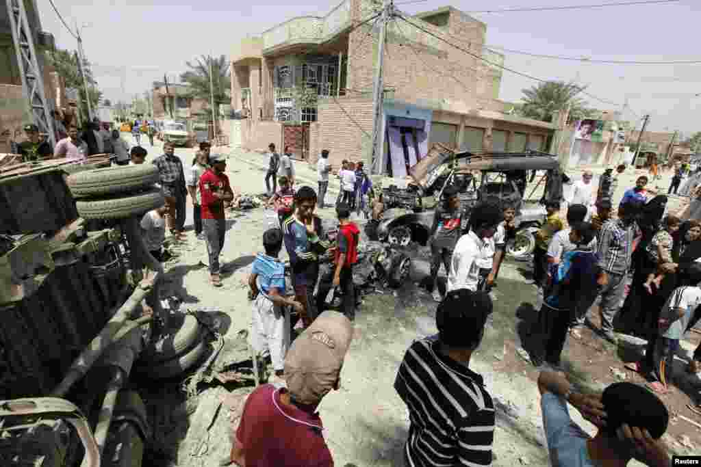 Residents gather at the site of a car bomb attack in Baghdad, April 15, 2013.