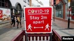 Papan peringatan untuk menjaga jarak sosial di tengah pandemi COVID-19 di Leicester, Inggris, 27 Mei 2021. (REUTERS/Andrew Boyers)