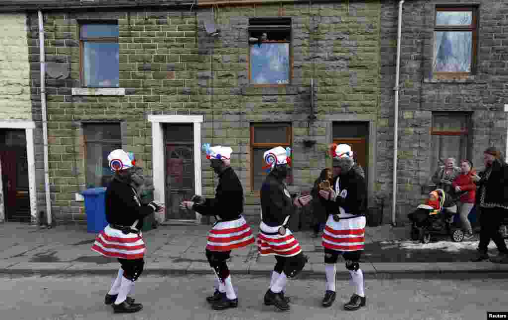 Members of the Britannia Coconut dancers perform on the roadside near Bacup, northern England. The group, which can trace its origins to the mid-1800s, dance along the town's roads every Easter Saturday following a tradition to mark out the boundaries of the town.