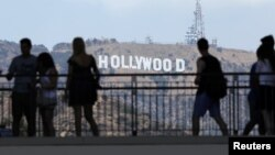 Tourists walk past the Hollywood sign as they visit a shopping complex along Hollywood Boulevard in Hollywood, California, Aug. 3, 2017.