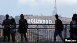 Turis dengan latar belakang tuisan Hollywood.