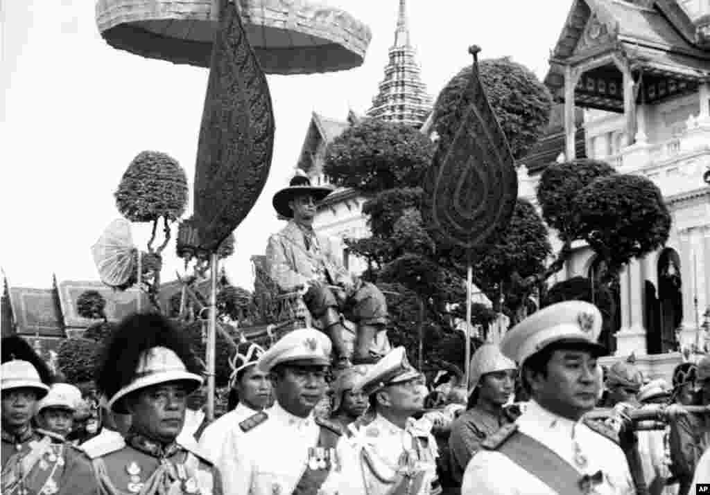 King Bhumibol Adulyadej is carried on the shoulders of Royal guards during a parade in Bangkok Dec. 7, 1963. The parade climaxed one week-long celebration of the King's 36th birthday.