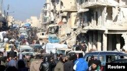 ພວກນັກລົບຕໍ່ຕ້ານລັດຖະບານ ຊີເຣຍ ແລະ ພົນລະເຮືອນ ພາກັນຄອຍຖ້າ ຢູ້ໃກ້ໆ ອາຄານຕ່າງໆ ທີ່ຖືກທຳລາຍ ເພື່ອຫວັງ ທີ່ຈະໄດ້ຖືກຍົກຍ້າຍ ອອກໄປຈາກ ເຂດປົກຄອງ ໂດຍ ພວກຕໍ່ຕ້ານລັດຖະບານຊີເຣຍ ທາງທິດຕາເວັນອອກ ຂອງ Aleppo, ວັນທີ 18 ທັນວາ 2016.