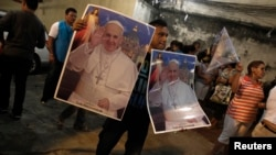 A man sells posters of Pope's visit of World Youth Day cross in Rio de Janeiro, July 18, 2013.