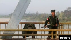 A Myanmar government soldier stands guard on Balaminhtin bridge over the Irrawaddy River near the city of Myitkyina in the north of the country after months of renewed fighting between government troops and the Kachin Independence Army, or KIA, February 2