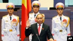 Vietnamese Prime Minister Nguyen Xuan Phuc takes the oath of office after being re-elected by the National Assembly in Hanoi, July 26, 2016.