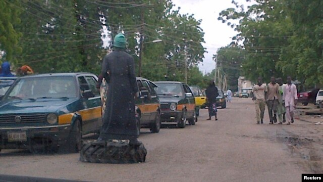 "Member of vigilante groups popularly called ""civilian JTF"" monitors traffic on used tire, Mafoni village, Borno state, Aug. 6, 2013."