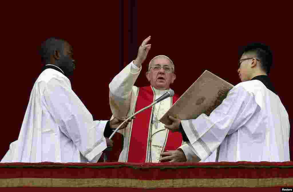 "Pope Francis makes a blessing as he delivers his first ""Urbi et Orbi"" (to the city and world) message from the balcony overlooking St. Peter's Square at the Vatican, Dec. 25, 2013"