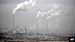 FILE - Smoke billows from chimneys of the cooling towers of a coal-fired power plant in Dadong, Shanxi province, China.