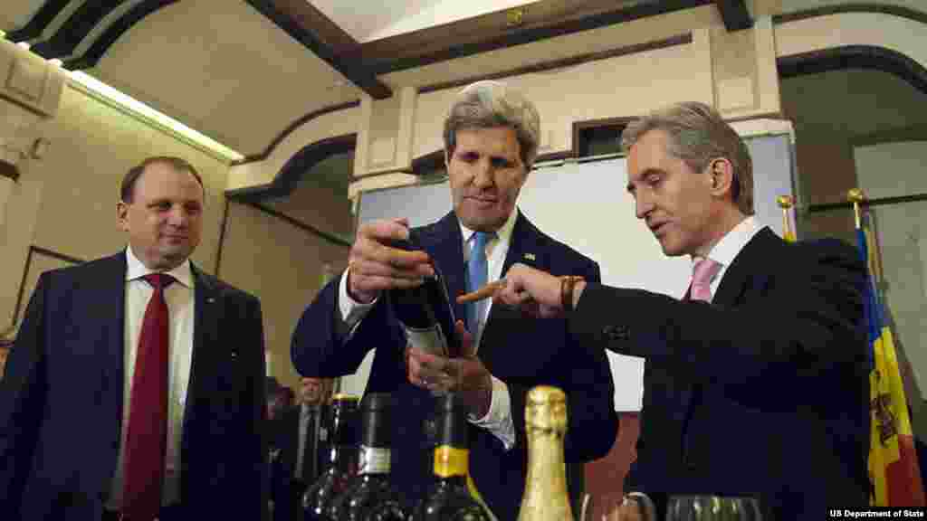 Moldovan Prime Minister Lurie Leanca, right, points out the label of a local wine to U.S. Secretary of State John Kerry as they sample some local vintages during an economic development event at the Cricova Winery outside Chisinau, on Dec.4, 2013.