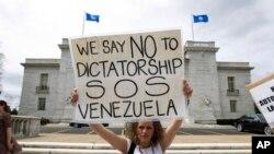 """Yon manifestan kap pwoteste kont rejim Prezidan Nicolas Maduro a, kenbe anlè yon ansèy ki ekri, """"nou di non ak diktati o Venezuela"""" devan building OEA, nan Washington kote yon rankont tap dewoule sou kriz venezuelyèn nan jedi 24 janvye 2019 la."""