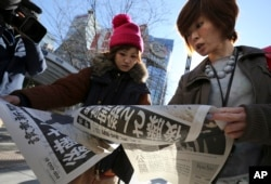 Japanese women react as they read extra newspapers in Tokyo reporting about an online video that purported to show an Islamic State group militant beheading Japanese journalist Kenji Goto, Feb. 1, 2015.