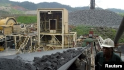 FILE - A worker at Ashanti Goldfield Company's big mine in Obuasi, Ghana, walks next to a conveyor belt carrying ore up to a processing plant, Oct. 23, 2003.