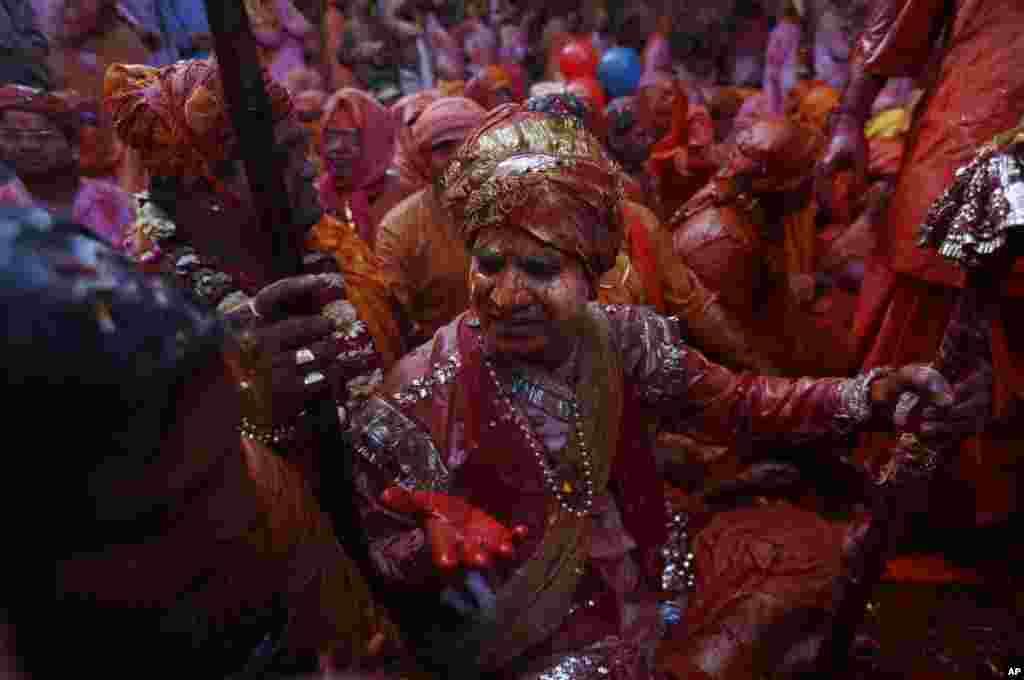 زنان و مردان هندی هنگام تجلیل از روز مذهبی هولی در شهر رادا در ۷۱ کیلومتری دهلی جدید