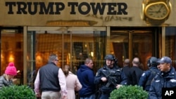 A heavily-armed New York City police officer stands guard outside the Fifth Avenue., public entrance to Trump Tower, Nov. 15, 2016, in New York.