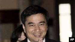 Thai Prime Minister Abhisit Vejjajiva greets as he walks on the hallway of the Government House in Bangkok, May 9, 2011