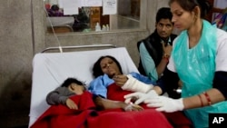 An injured passenger and her son share a bed as they are treated at a hospital in Kanpur, in the northern Indian state of Uttar Pradesh, India, Nov. 21, 2016.